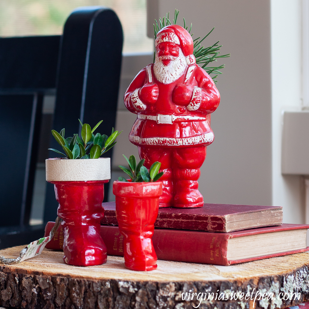 Two vintage Santa boots with Boxwood and a vintage Santa candy holder