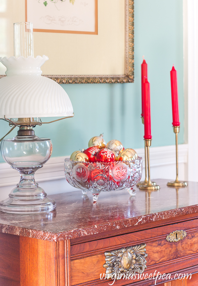 Decorations on a chest for Christmas including a trio of red candles in brass candle holders and an antique glass bowl filled with vintage red and gold Christmas ornament.