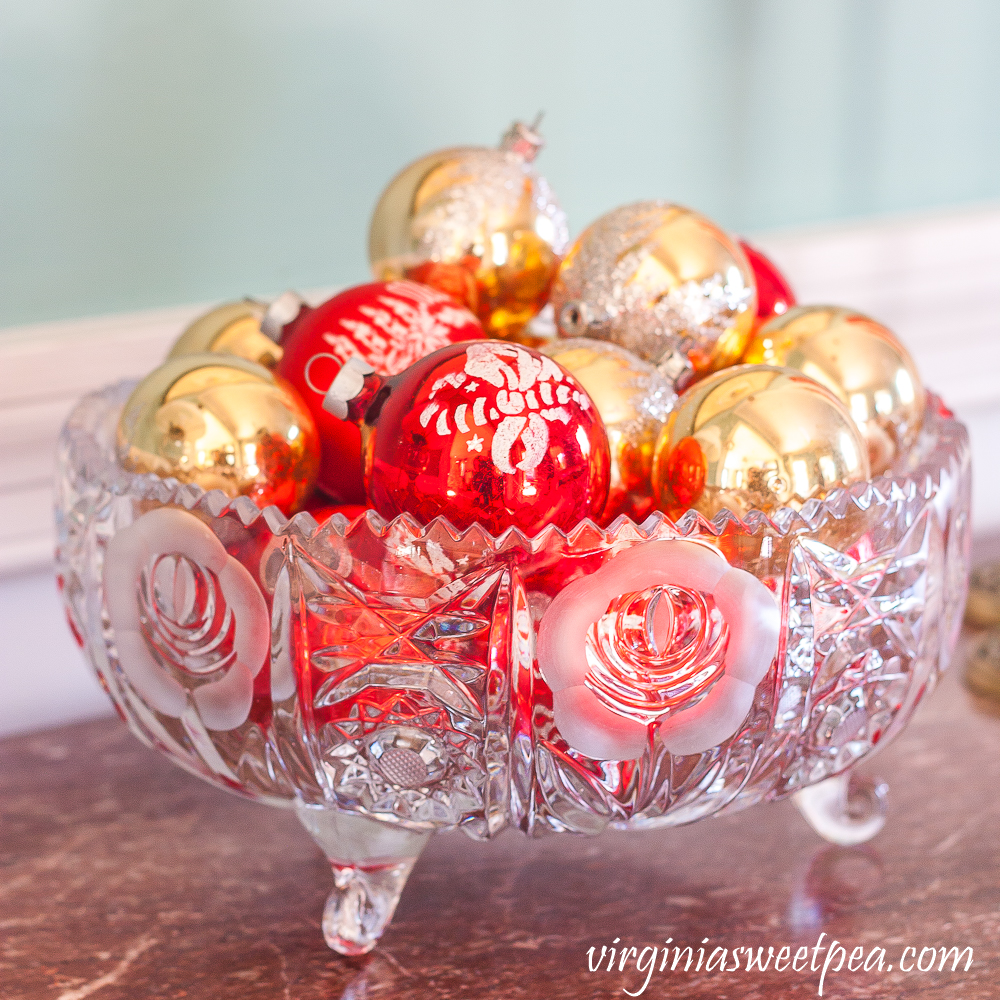 Antique glass bowl filled with vintage red and gold Christmas ornaments