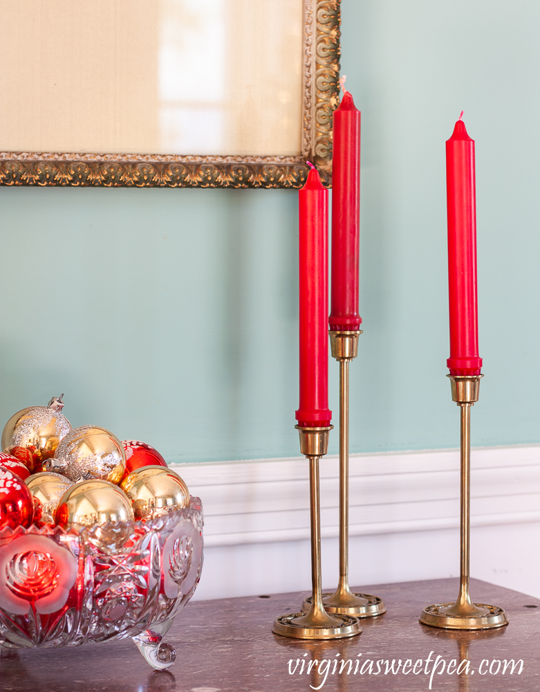 A trio of brass candle holders with a glass bowl filled with vintage red and gold Christmas ornaments in a dining room decorated for Christmas.