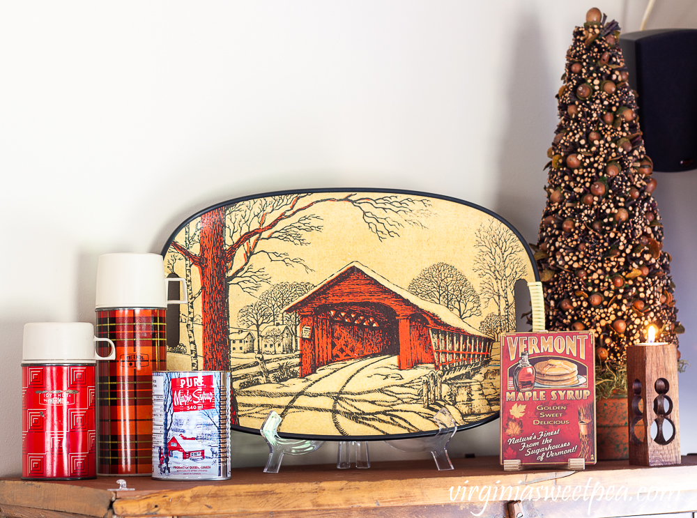 Red thermoses, covered bridge tray, tree decorated with acorns and twigs, handmade snowman candle holder, and Vermont maple syrup postcard.
