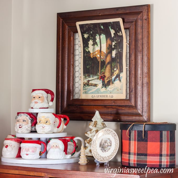 Vintage Santa mugs with vintage Christmas candles, a Knowles plate, vintage Coke lumber poster, and tartan sewing basket