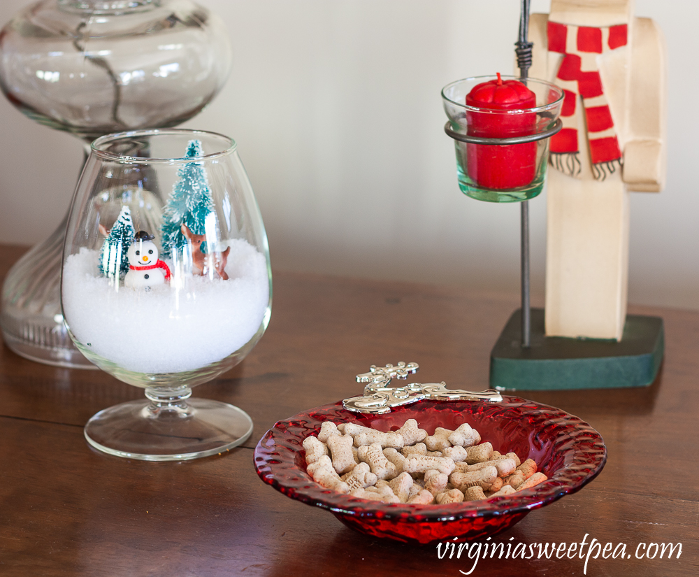 Dog treats in a reindeer bowl with snowman Christmas decor