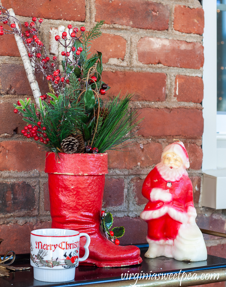 Large vintage Santa boot with greenery, vintage Christmas mug, and vintage Santa candle