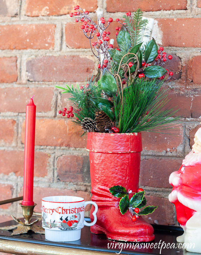 Large vintage Santa boot with greenery, vintage Christmas mug, brass holly candle holder with red candle.