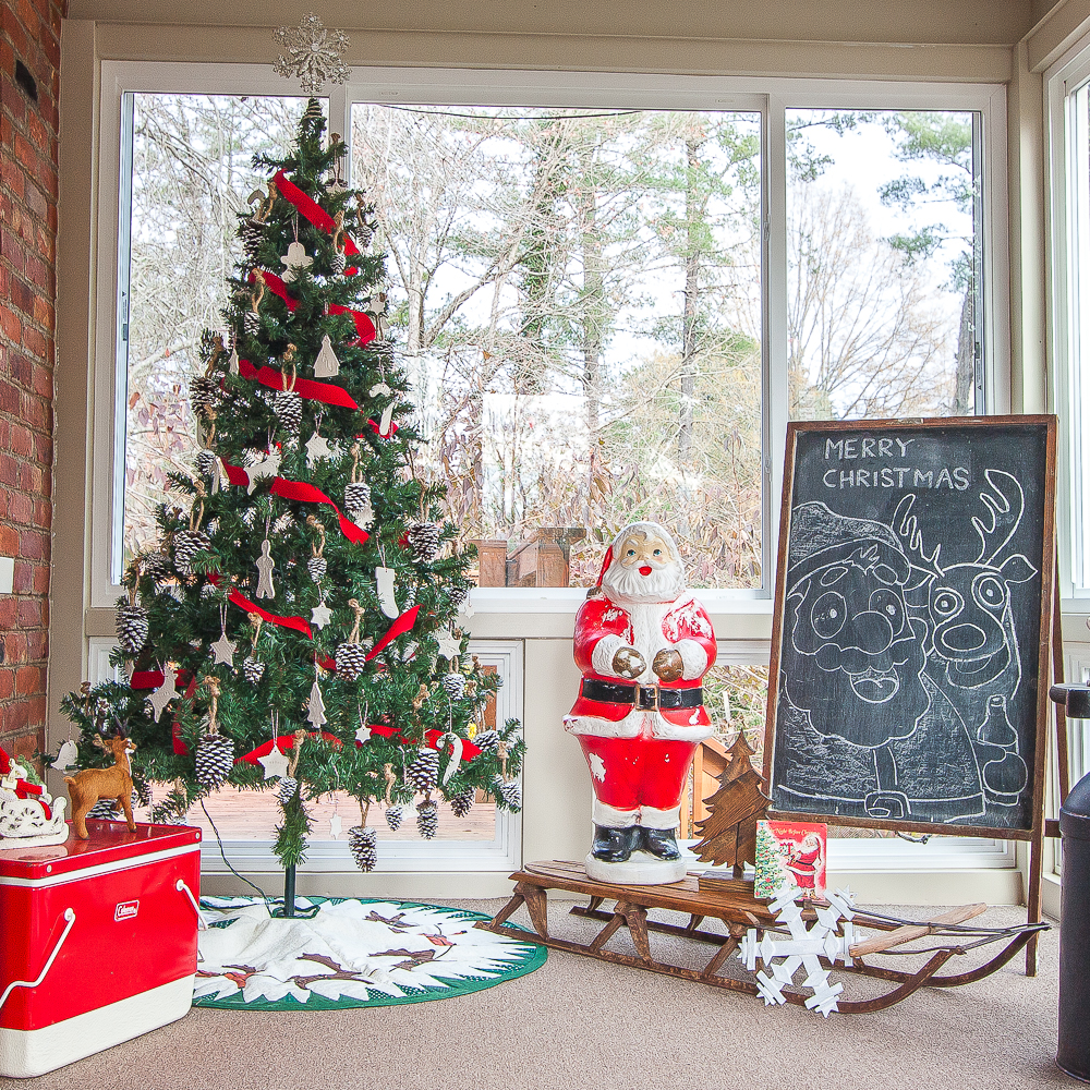 A porch decorated for Christmas with a tree with handmade ornaments, handmade tree skirt, blowmold Santa, and more vintage Christmas decor
