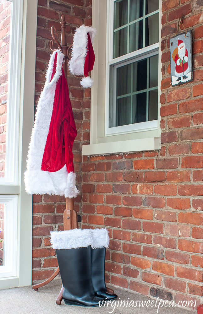 Santa outfit and boots displayed on a porch decorated for Christmas