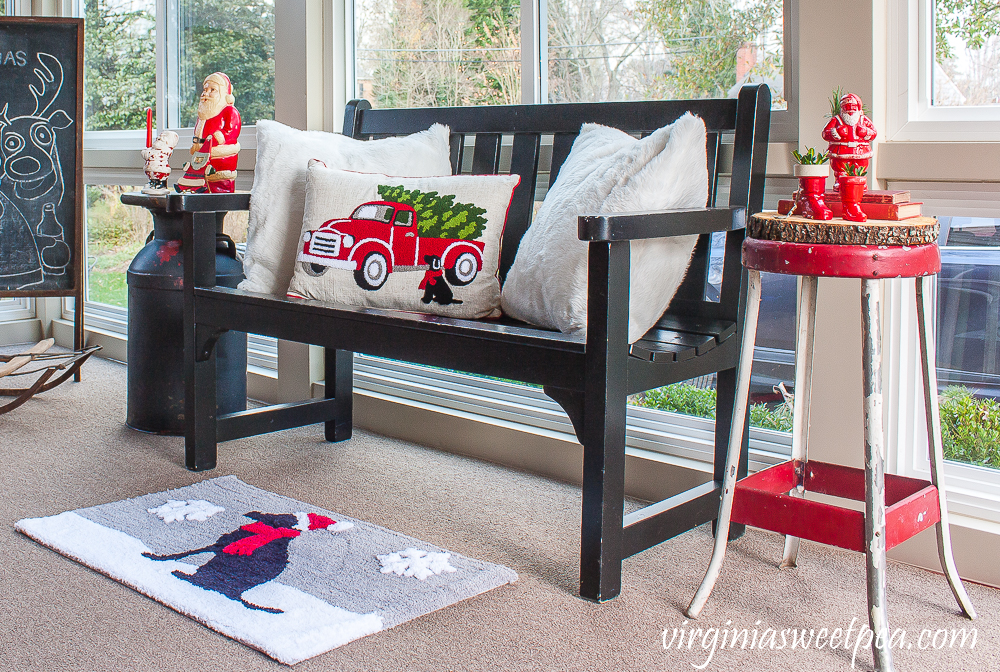 Porch decorated with a bench with a red truck and black lab and a black lab Christmas rug