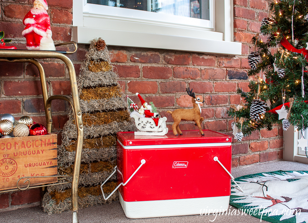 Vintage red Coleman cooler used on a porch decorated for Christmas