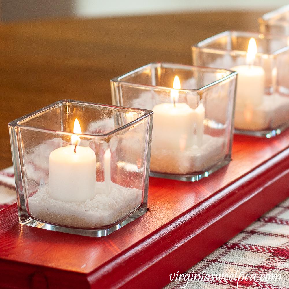 White votive candles in glass votives with Epsom salt on a red handmade glass votive holder.