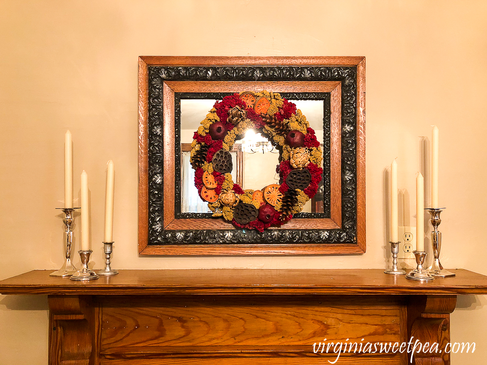 Mantel Decor in a 1912 House with dried floral wreath on an antique mirror with silver candlestick holders and white candles