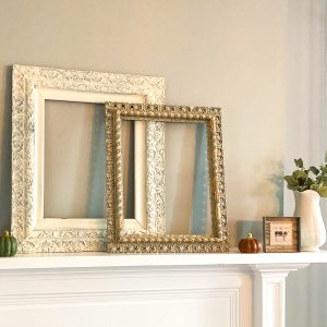 Two antique frames, one white, one gold, with a pumpkin, cow picture, and white pitcher filled with Eucalyptus