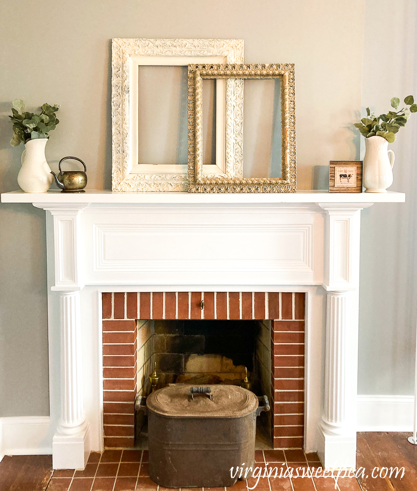 Mantel in an 1857 farmhouse styled with antique frames, white pitchers, brass kettle, copper pot