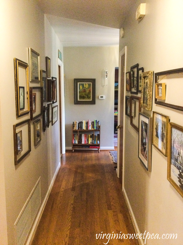 Hallway lined with frames hanging on the wall