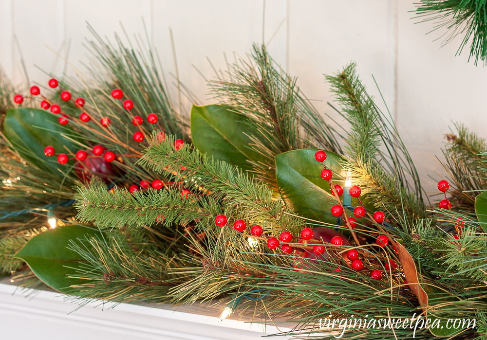 Realistic faux evergreen garland embellished with faux berries, apples, and Magnolia leaves.