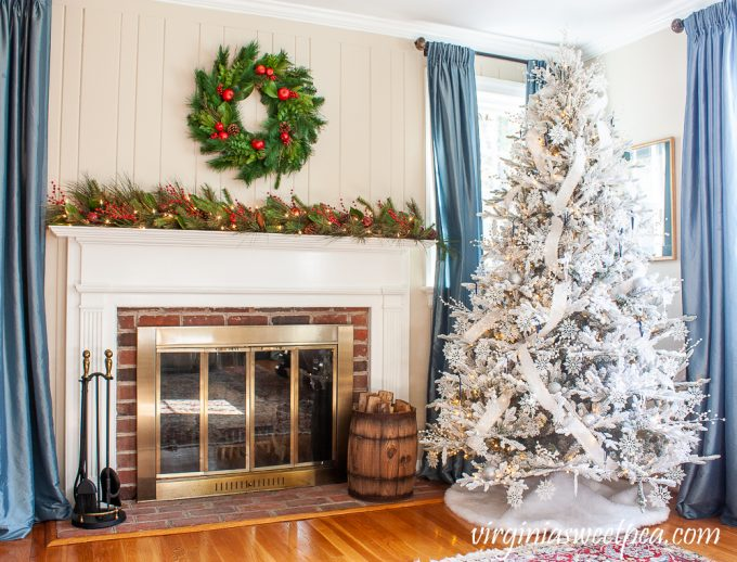 Christmas mantel with Williamsburg wreath and lighted garland on the mantel with red berries, Magnolia, and pine cones and a flocked Christmas tree decorated with snowflakes