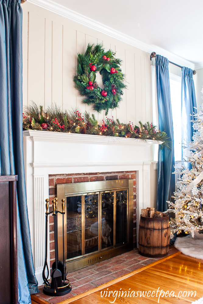 Christmas mantel with Williamsburg wreath and lighted garland on the mantel with red berries, Magnolia, and pine cones.