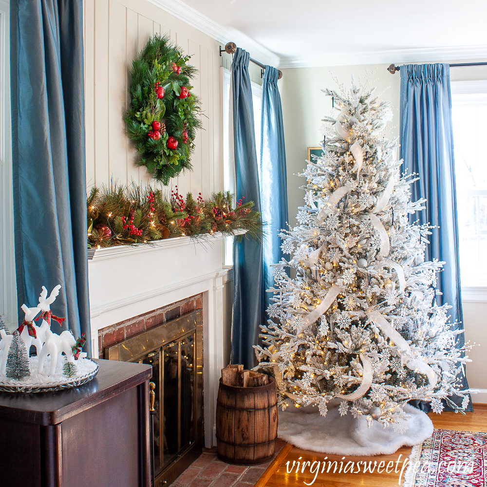 Flocked Christmas tree beside a mantel decorated for Christma