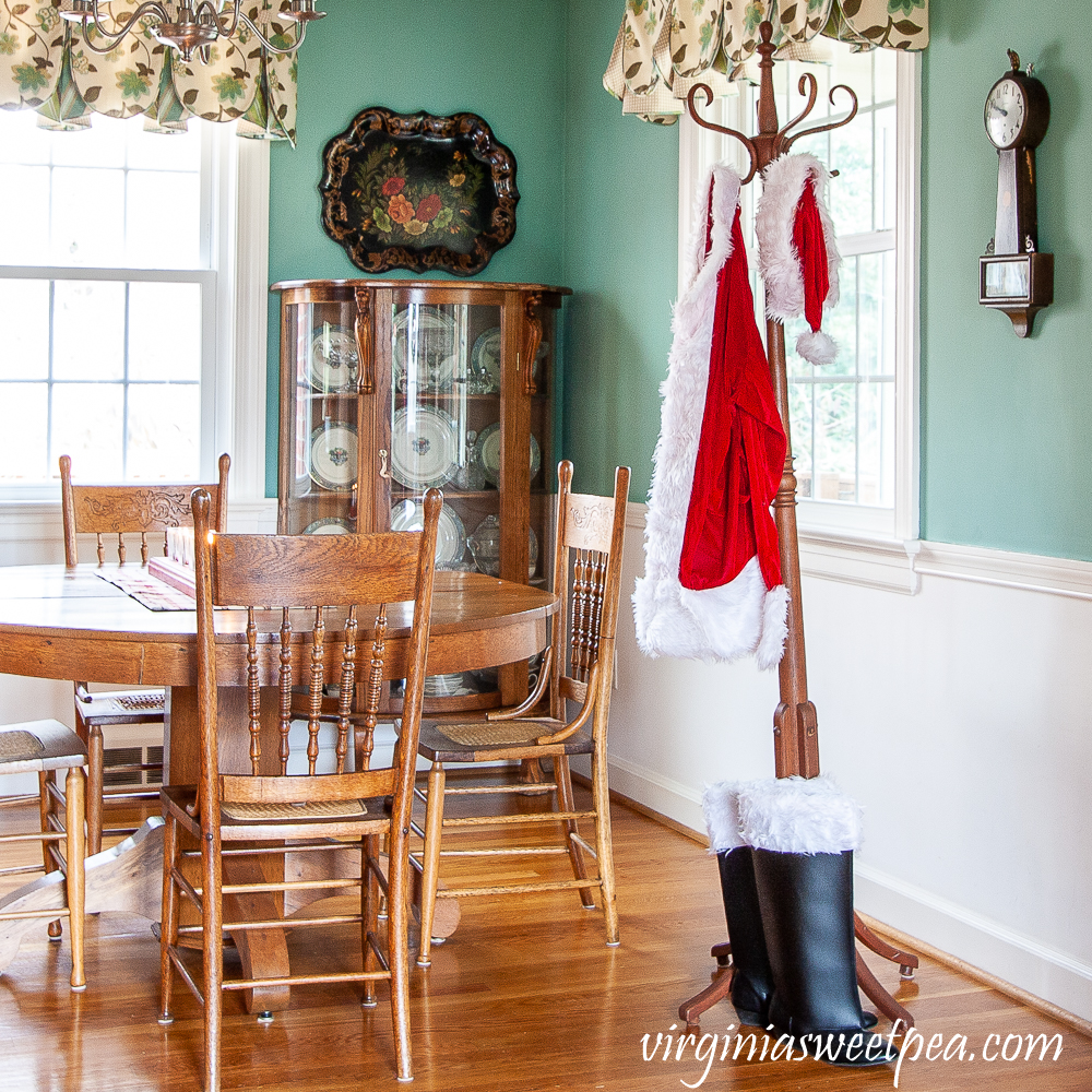 A Santa suit hanging on a coat rack along with Santa's boots