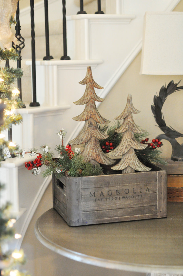 Crate decorated for Christmas with two wooden trees and greenery.