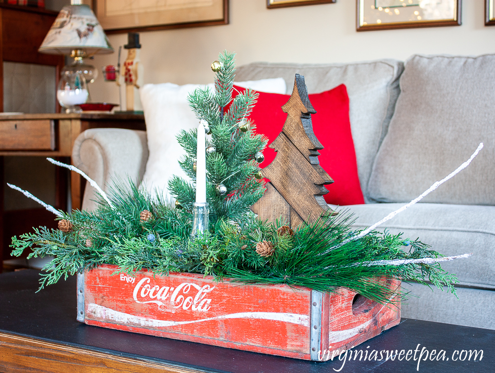 Vintage Coca-Cola crate decorated for Christmas with a wood tree, vintage Coke bottle, and greenery.
