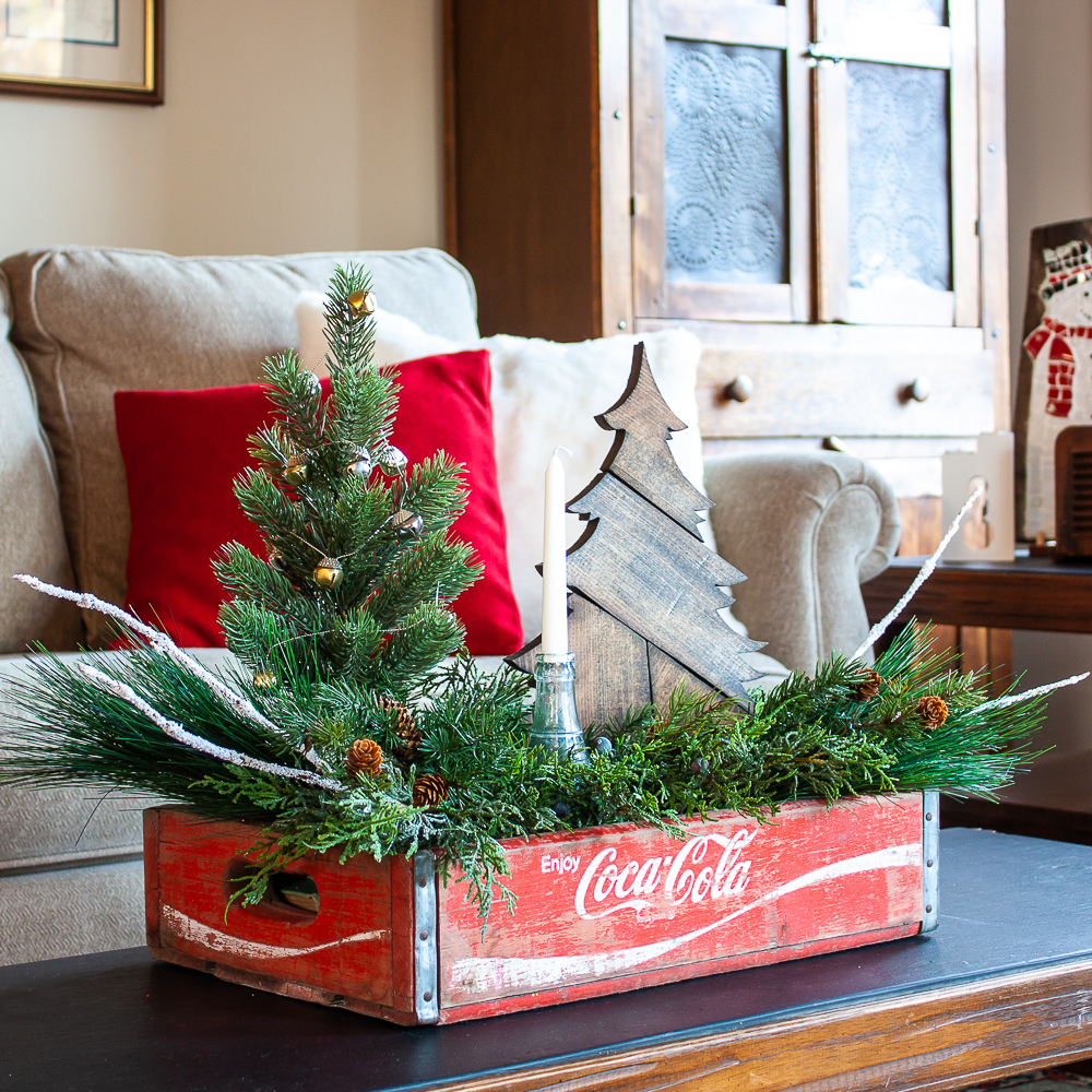 Vintage Coca-Cola crate decorated for Christmas on a coffee table