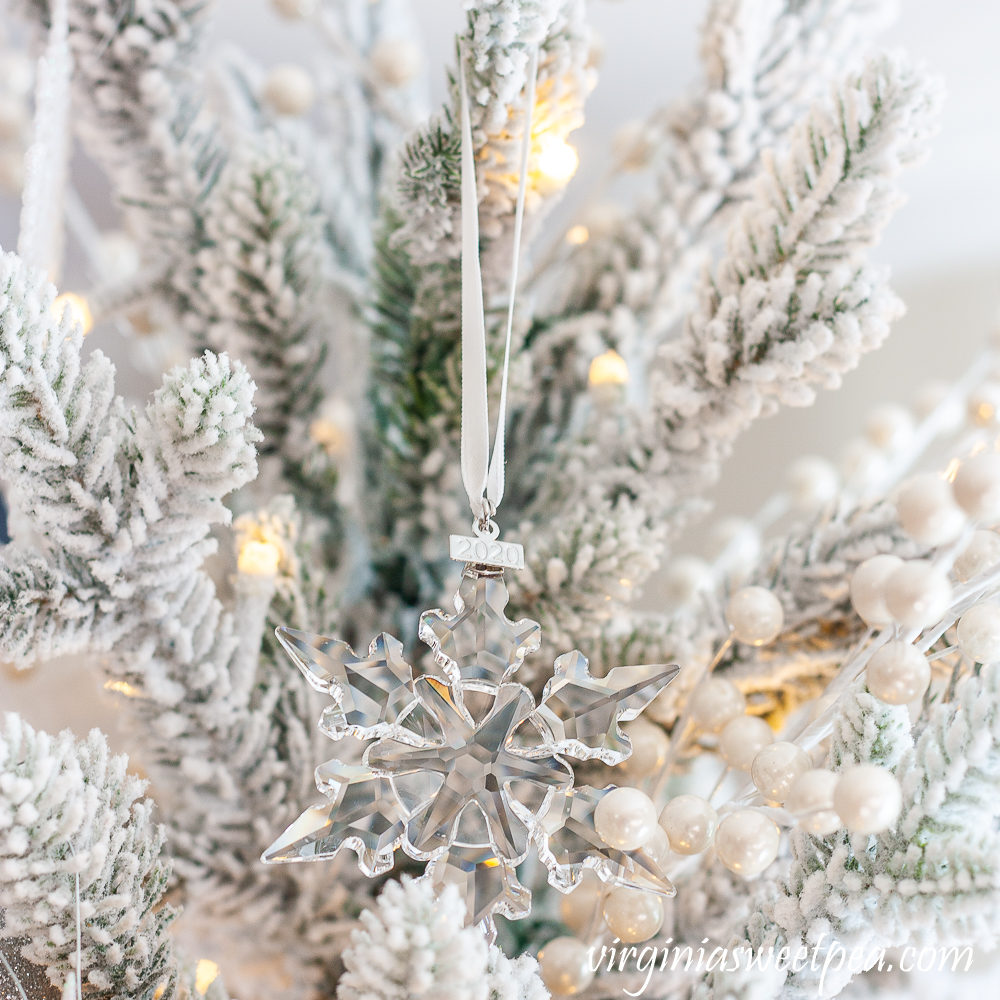 2020 Swarovski snowflake ornament on a tree decorated with a snowflake theme