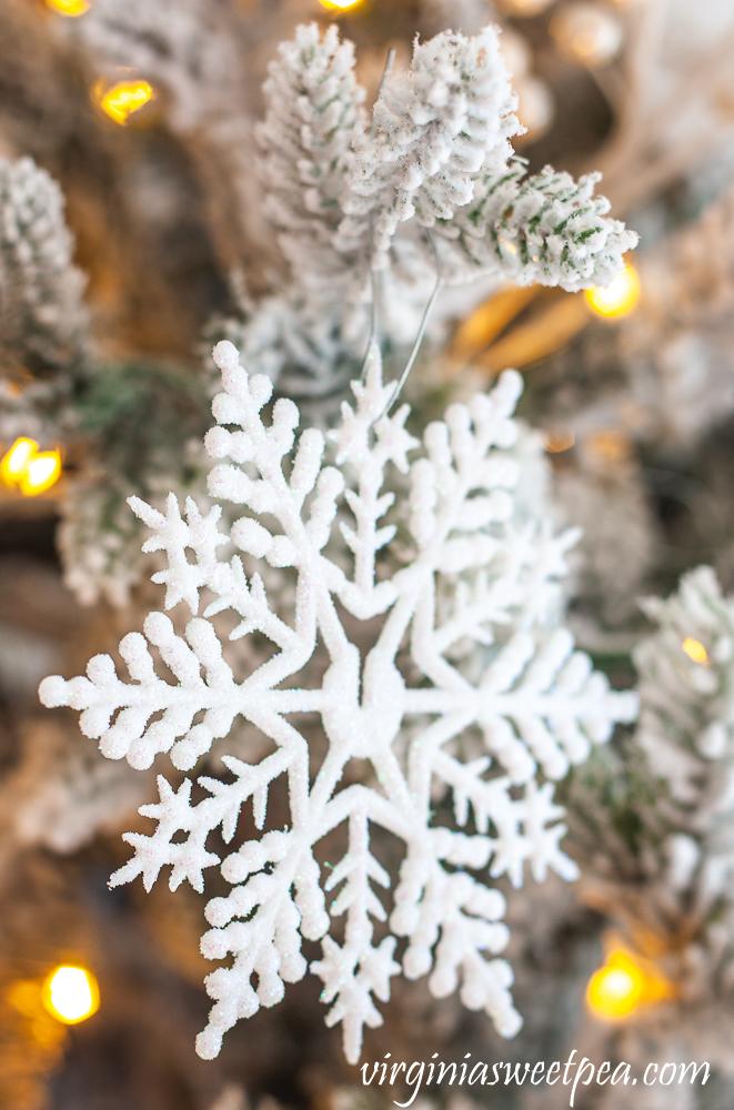 White snowflake on a flocked Christmas Tree
