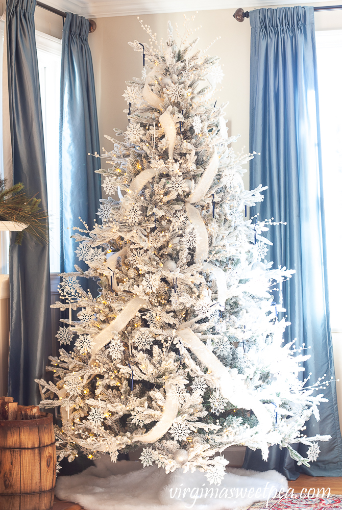 Flocked Christmas tree decorated with a snowflake theme