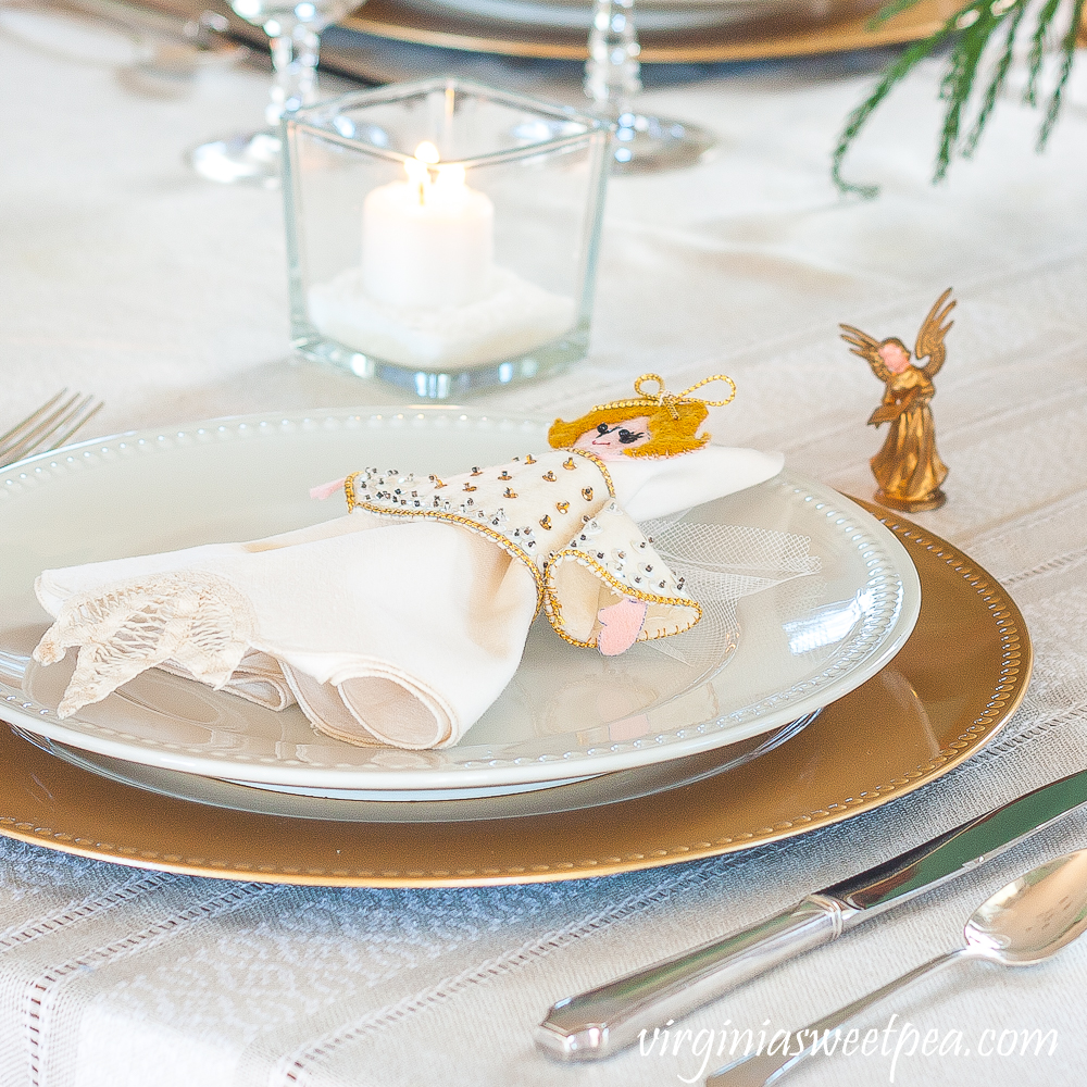 Christmas place setting with vintage silver, a gold charger and white plate, napkin with a vintage 1970s angel napkin holder and a vintage musical angel ornament