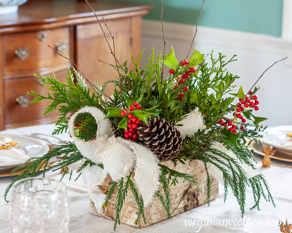 Christmas centerpiece with greenery, Holly, pinecones, twigs, and white ribbon trimmed with gold
