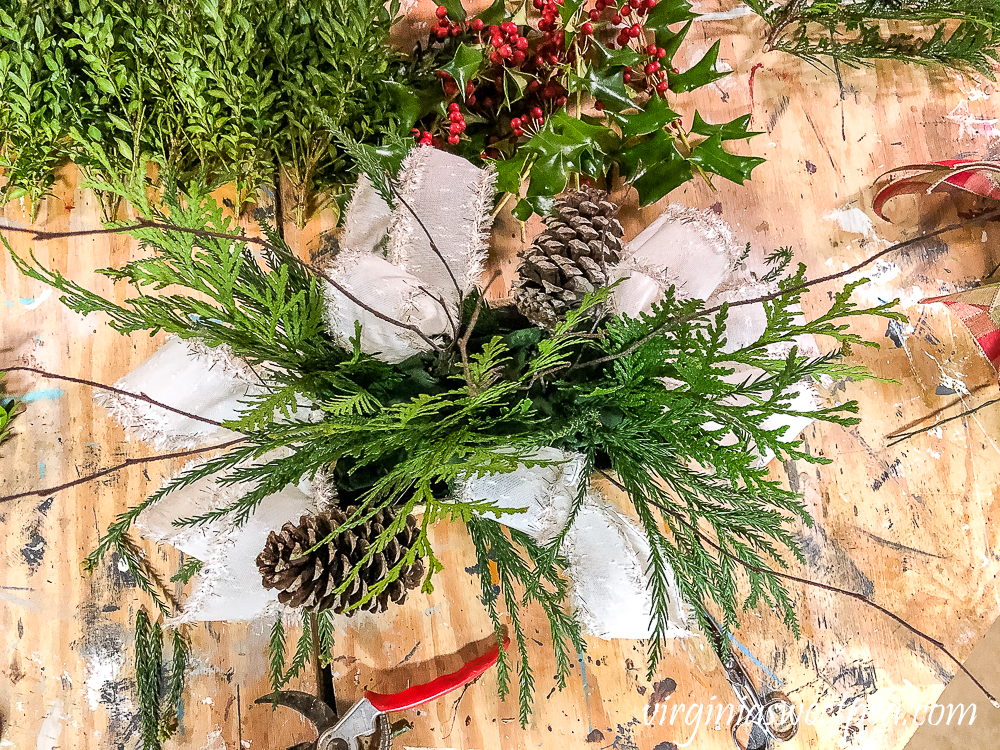 Greenery, pinecones, twigs, in a birch bark floral container