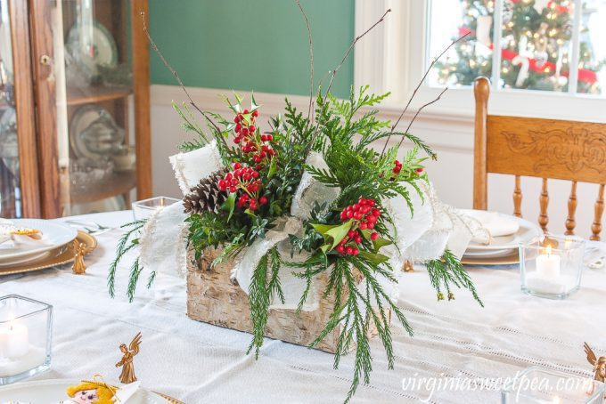 Christmas centerpiece in a Birch bark box with greenery, Holly, pinecones, twigs, and white ribbon trimmed with gold