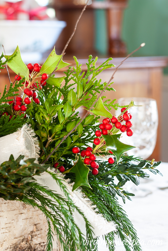 Side view of a Christmas centerpiece in a Birch bark box with greenery, Holly, twigs, and white bows