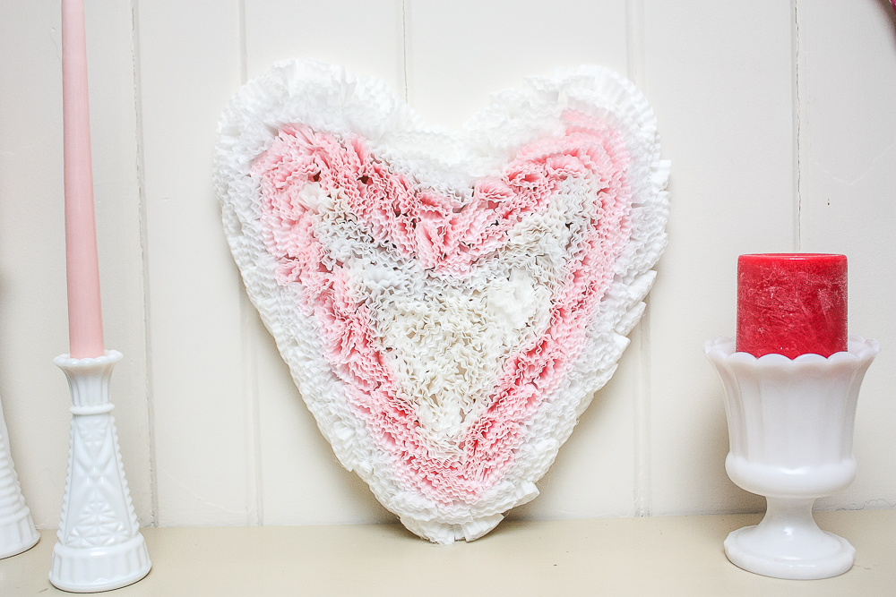 Cardboard heart decorated with pink and white cupcake liners on a mantel with white milk glass and pink and red candles
