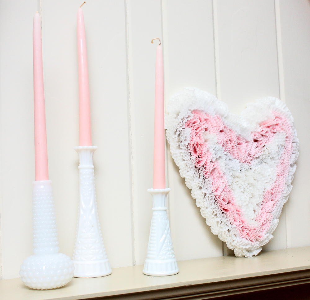 Three milk glass vases with pink candles and a cardboard heart decorated with pink and white cupcake liners