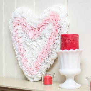 Handmade cupcake liner heart displayed with a milk glass compote with a dark pink candle and a clear votive with a matching votive candle