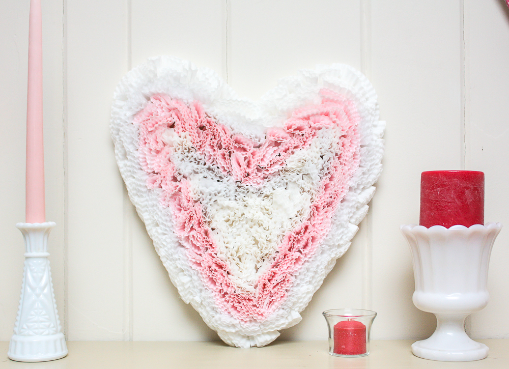 Valentine's Day cupcake liner heart on a mantel with milk glass vases and candles
