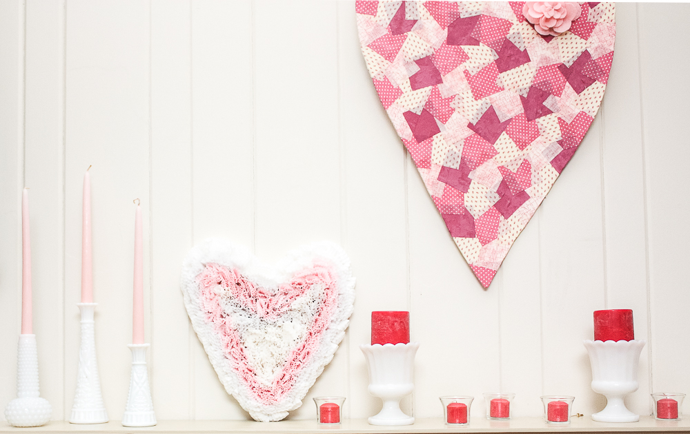 Valentine's Day mantel decor with two handmade heart crafts and milk glass vases with candles