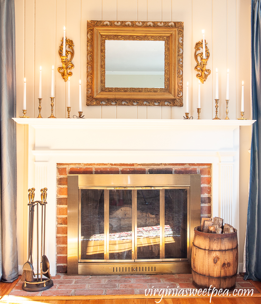 Mantel Decorated for winter with gold, brass, and white candles.