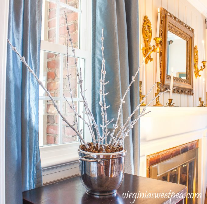 Winter Decor with icy branches, white candles, and gold