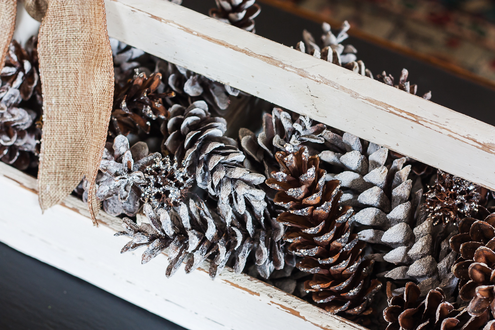 Vintage toolbox decorated for winter with glittered and snow-kissed pinecones.