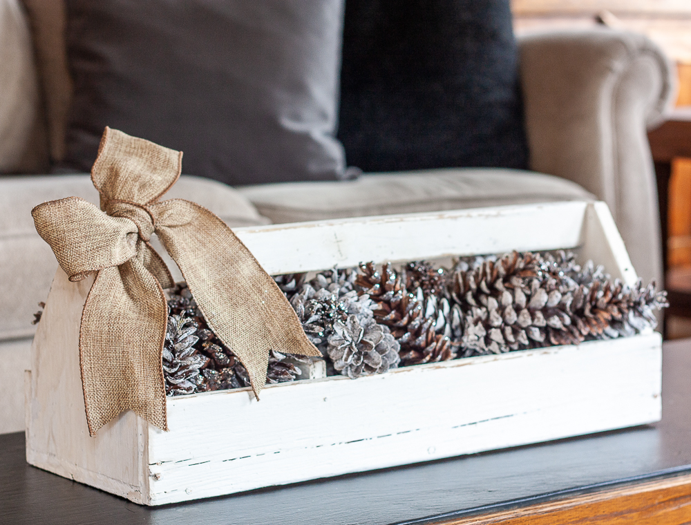 Vintage toolbox decorated for winter with glittered and snow-kissed pinecones and a burlap bow.