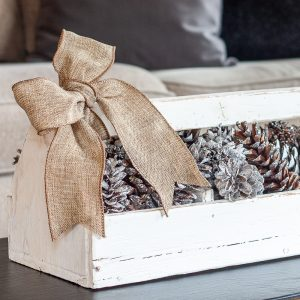 Handmade white toolbox filled with pinecones and glittered Sweet Gum balls