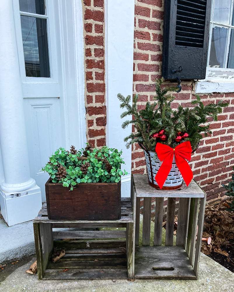 Vintage toolbox decorated with Eucalyptus and pinecones and olive bucket filled with Christmas greenery on crates.