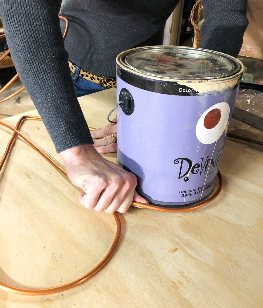 Using a paint can to make the top of a heart with copper tubing