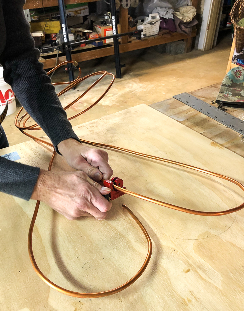 Using a pipe cutter to cut a copper pipe