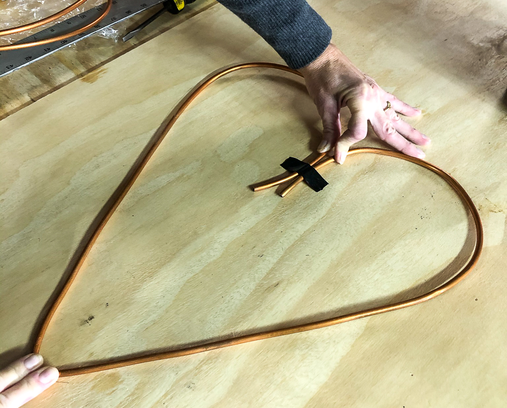 Heart formed from copper wire taped to a piece of plyboard with electrical tape
