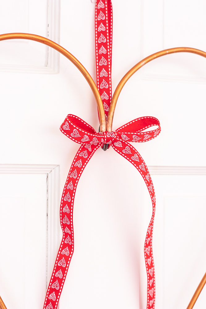 Valentine's Day red and white heart ribbon decorating a copper pipe heart wreath