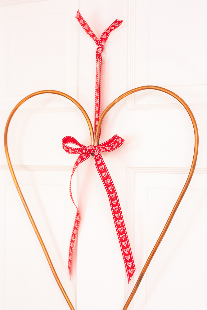 "Valentine's Day wreath made from 1/4"" copper pipe decorated with a red ribbon with white hearts"
